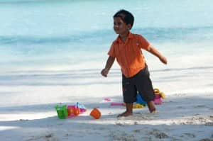 Boy on beach at Constance Halaveli Resort