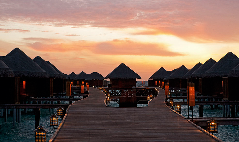 The sun sets over Halaveli's water villas