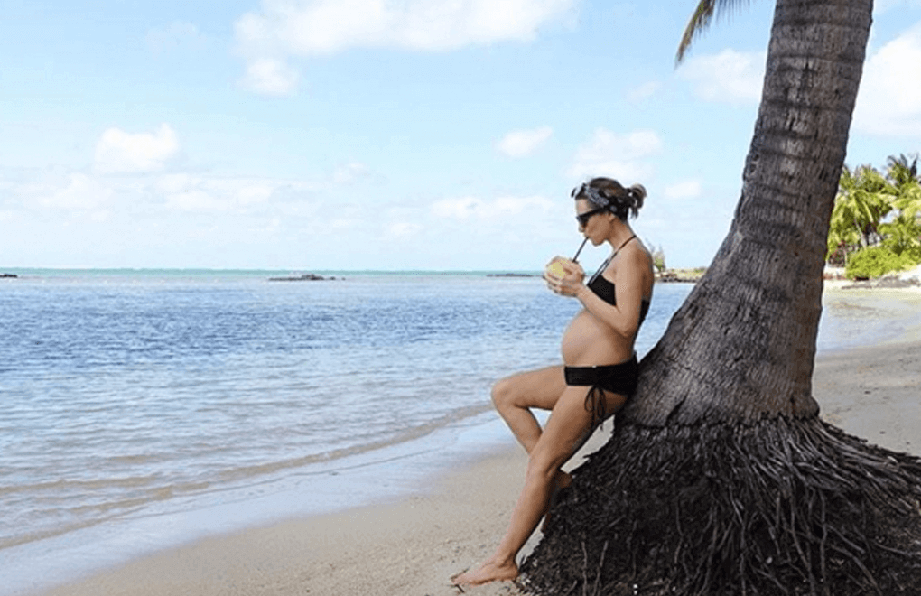 Laura Fantacci drinking some coconut water during her stylish babymoon