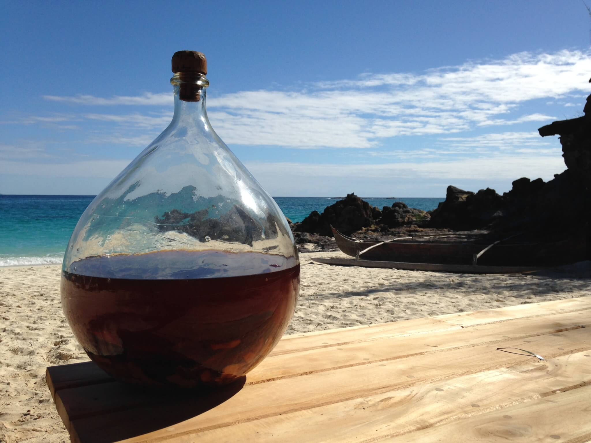 Bottle of homemade rum by the sea